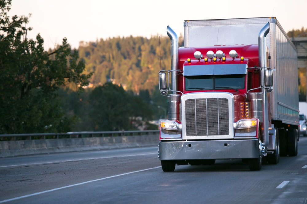 A red semi truck on the road.